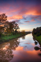 Wonderful sunset colors of fall with river reflections