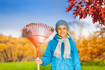 Portrait of small smiling boy with rake in park