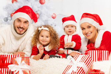 Family of four with presents and Christmas tree