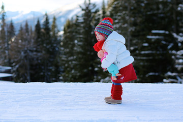 Little girl playing in winter forest