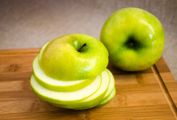 The apple cut with circles on a wooden board