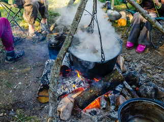 Cooking in a hike in the cauldron hanging over the fire