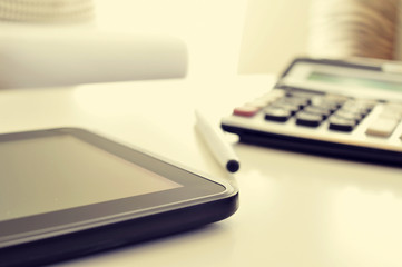 tablet and calculator on an office desk