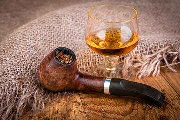 overview of cognac  and smoking pipe on wooden background.