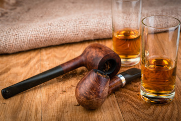 smoking pipes  and  cognac or brandy glasses on vintage style