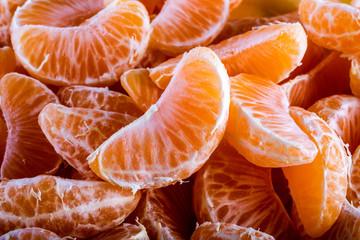 Tangerine or mandarin orange segments peeled close up background
