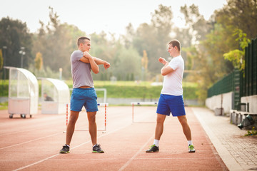 Two young men stretching before or after sport training