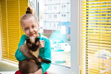 Девочка с кошкой сидит у окна
