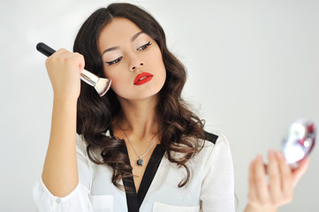 Portrait of young attractive woman with makeup brush over white