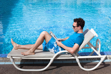 young man reading magazine near swimming pool in luxury hotel