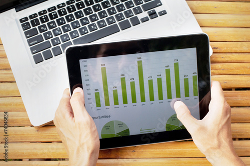 hands of farmer with tablet with infographics on the screen - 74046834