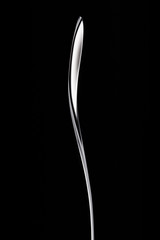 Silver spoon on pure black background