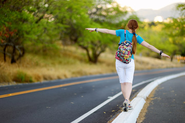 Young tourist hitchhiking along a road