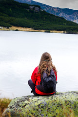Young woman admiring the stillness of mountain  lake