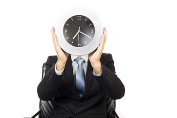 Closeup of businessman covering his face with a wall clock
