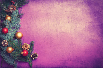 Pine branch and toys on violet background.