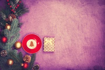 Cappuccino with christmas tree shape and gift box on violet back