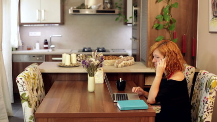 Woman on the phone with laptop at home office