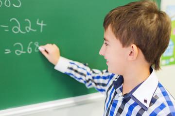 little smiling schoolboy writing on chalk board