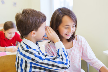 smiling schoolboy whispering to classmate ear