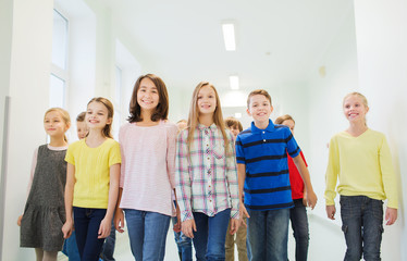 group of smiling school kids walking in corridor