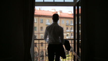 Silhouette of a man wears a jacket standing on the balcony