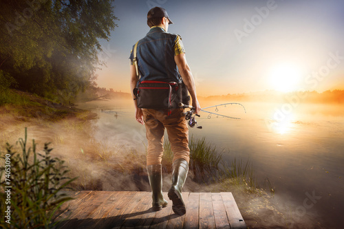 Young man fishing at misty sunrise - 74053090