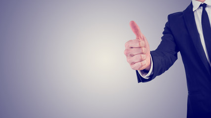 Businessman giving a thumbs up gesture in a business motivation