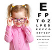 Smiling girl putting on glasses with blurry eye chart behind her - 74055248