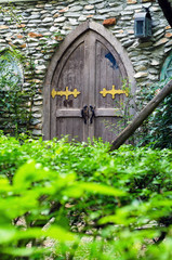 Wooden door in castle with stone wall