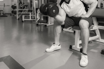 Muscular arm in the gym. Hand holding a dumbbell