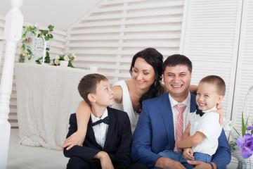 Happy parents sitting with their children
