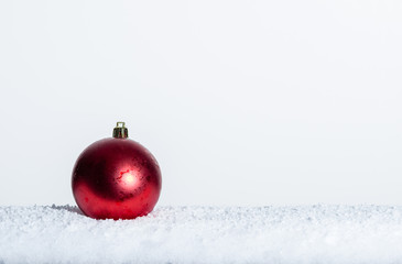 Single red Christmas ornament on snow