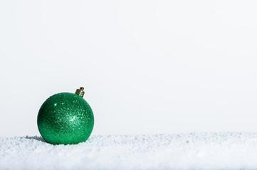 Single green Christmas ornament on snow