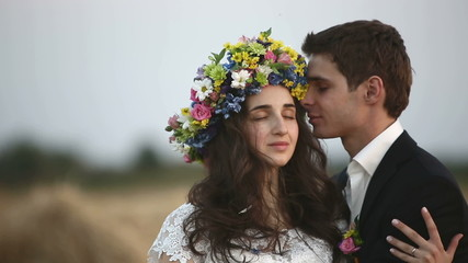 The man wears a wreath of flowers on the head of the girl