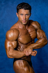 Handsome muscular bodybuilder demonstrates his muscles.