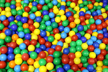 lots of blue green red yellow colored spheres into a pool of bal