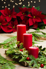 Red candle centerpiece with greens and red balls