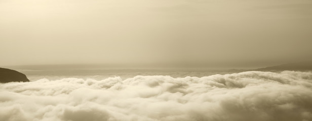 View of the sky above the clouds in sepia tone