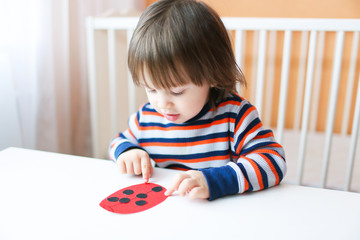 Lovely little boy made paper ladybug
