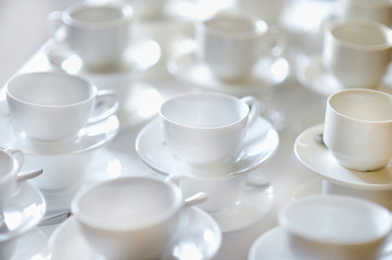 Many rows of pure white cups and saucers