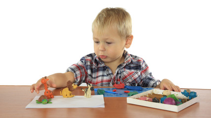 little boy sculpts from plasticine  animals