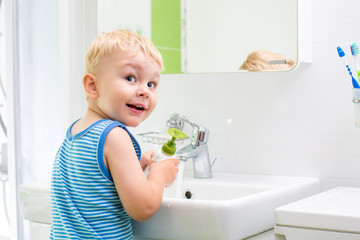 kid washing his face and hands in bathroom