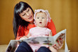 mother reading to baby girl