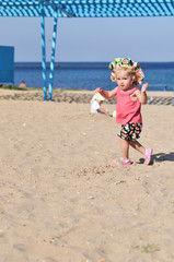 baby girl running on the beach