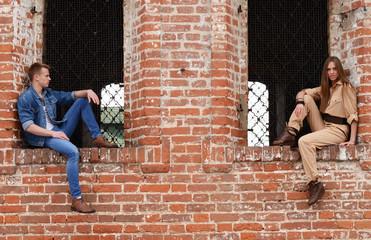 Young enamoured pair a brick wall