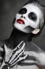 Young woman with dead mask skull face art. Halloween face