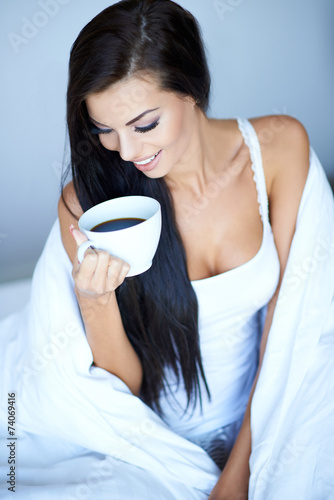 Happy Woman Wrapped in Blanket with Cup of Coffee - 74069416