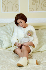 woman resting in bed with a doll