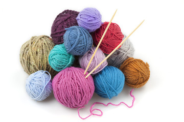 bunch of colored balls of yarn with two knitting needles